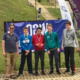 4 students and teacher at base of dry ski slope with medals